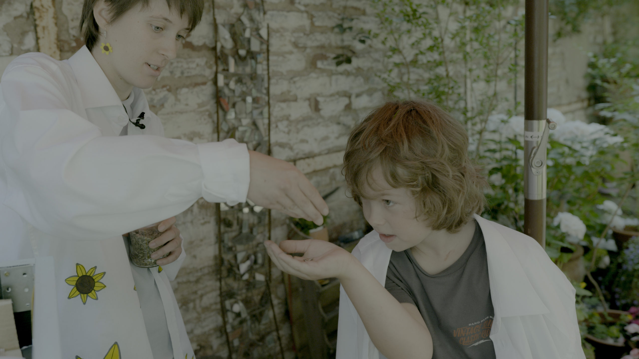 Julia (l.) verteilt Sonnenblumensamen an die Jungforscher