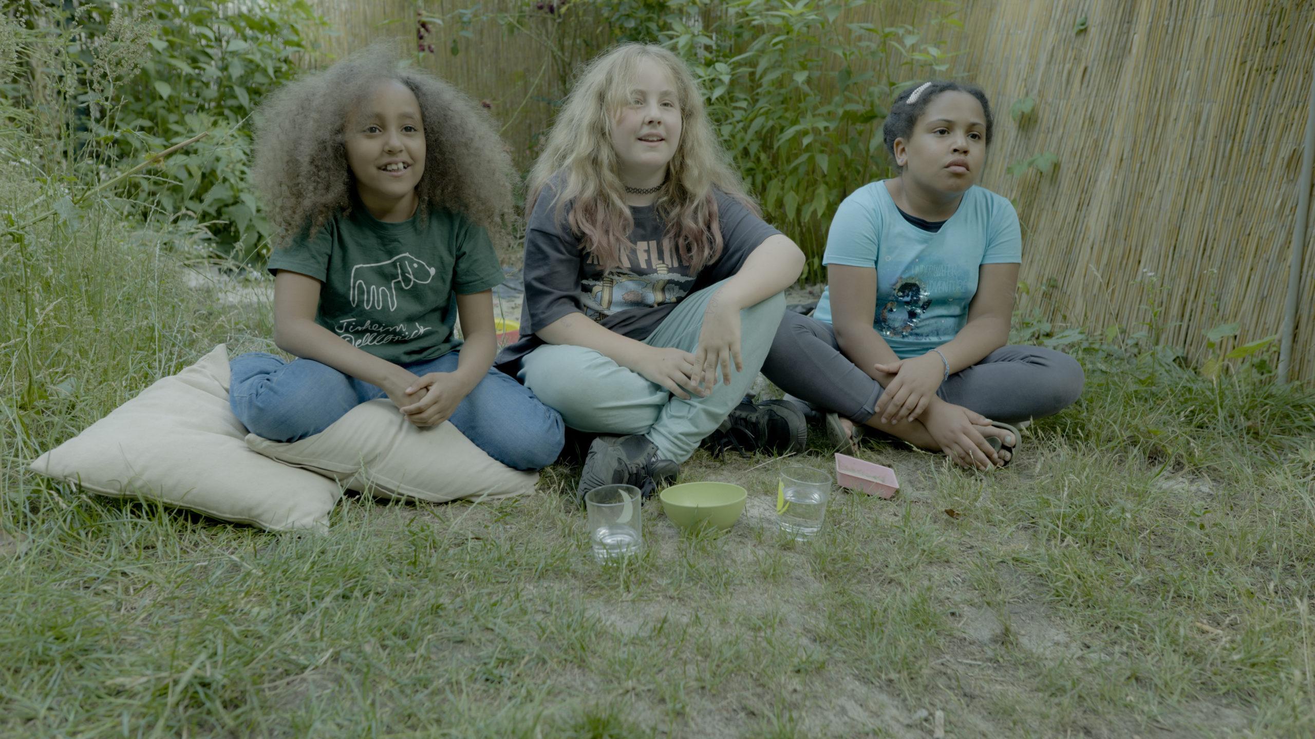 Laura (v.l.), Mila und Zoha beobachten wie die Sonnenblumensprossen im Clip tanzen